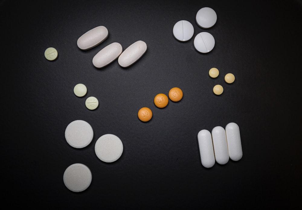 white and orange medication pill on black surface